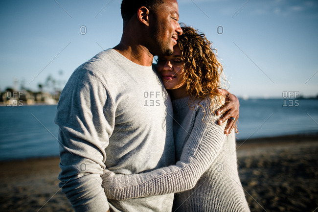 Multi racial couple embrace on beach at sunset