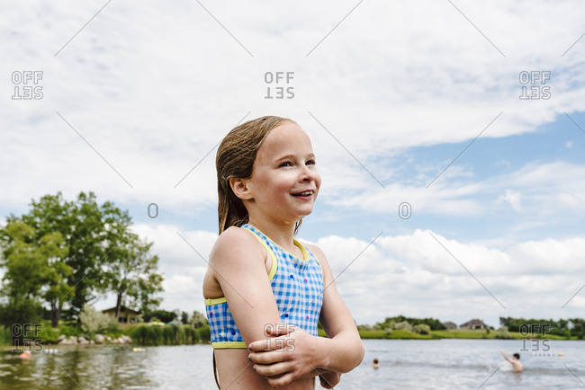 Little girl takes swim break on shore of lake during summer
