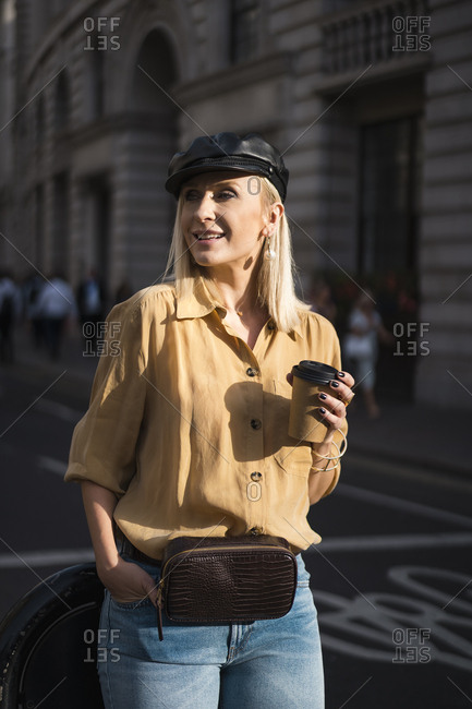 Elegant blond woman walking in the city drinking a coffe to go. London. UK