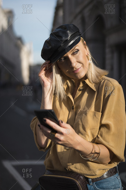 Elegant blond woman walking in the city using mobile phone. London. UK