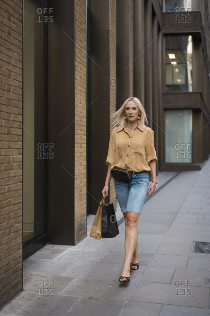 Elegant blond woman walking in the city during a shopping day. London. UK