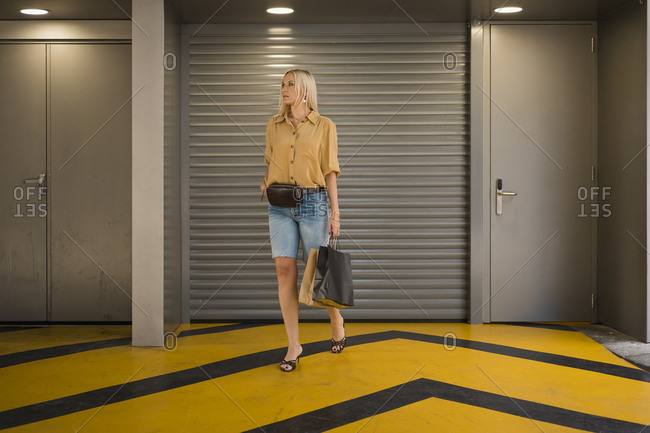 Elegant blond woman walking through a car park after a day of shopping