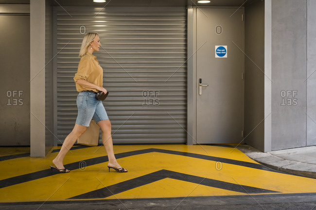 Elegant blond woman walking through a car park