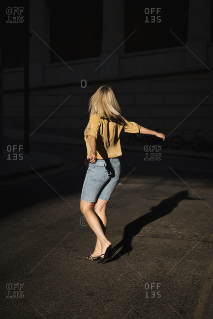 Blonde woman dancing in the streets of London