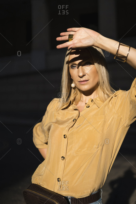 Woman posing to block the sun from her eyes