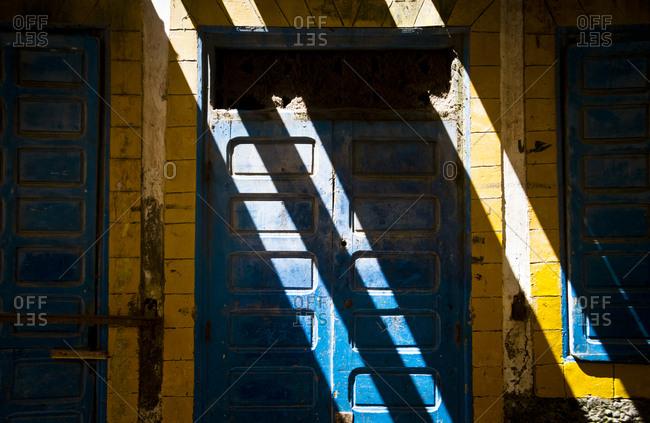 Sunlight falls across a blue door in Essaouira, Morocco, Africa