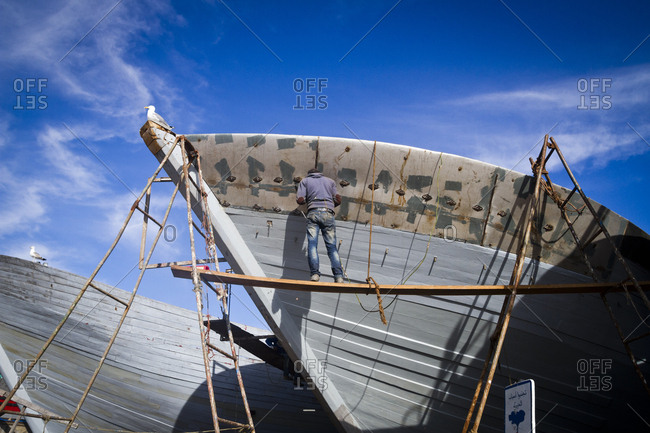March 28, 2013: Repairing a boat at the harbor in Essaouira, Morocco, Africa
