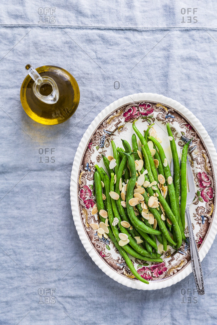 Green beans with almonds and bottle of oil