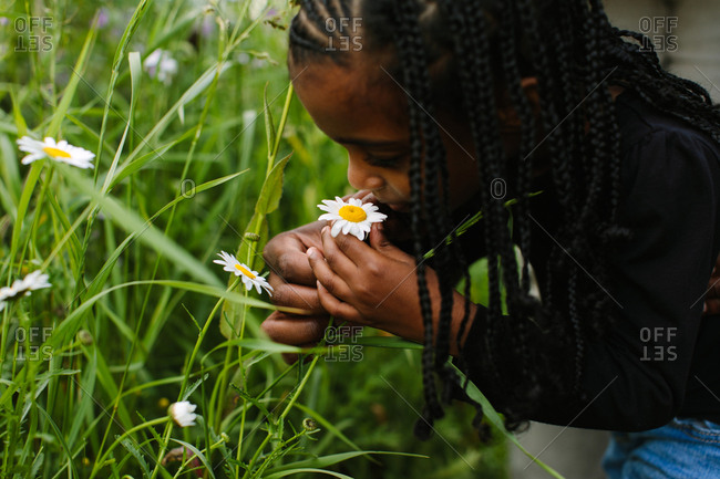 A close up of a young girl smelling a wild flower