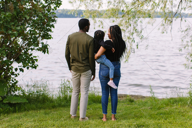 A family of three looking at the lake with their backs to the camera