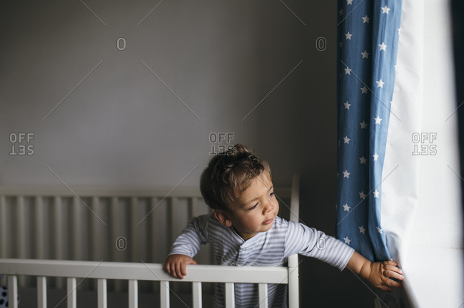 Baby boy in cot bed playing with curtains