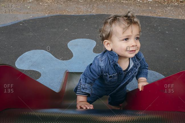 Little Boy climbimg up The Slide