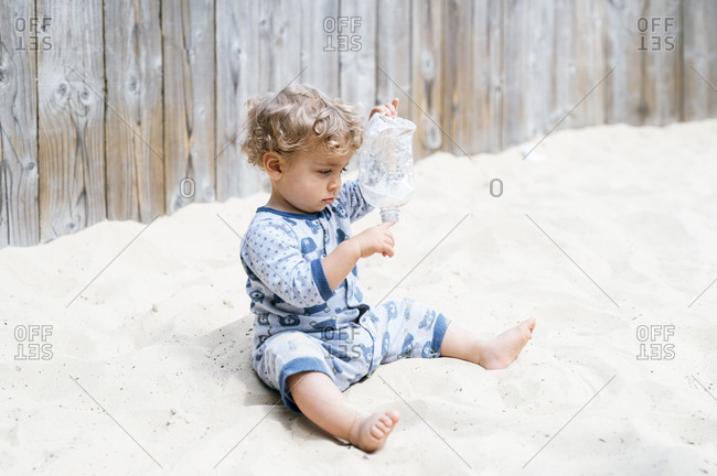 Baby boy playing with plastic bottle in sandpit