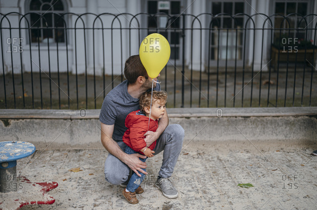 Baby boy with dad holds yellow balloon
