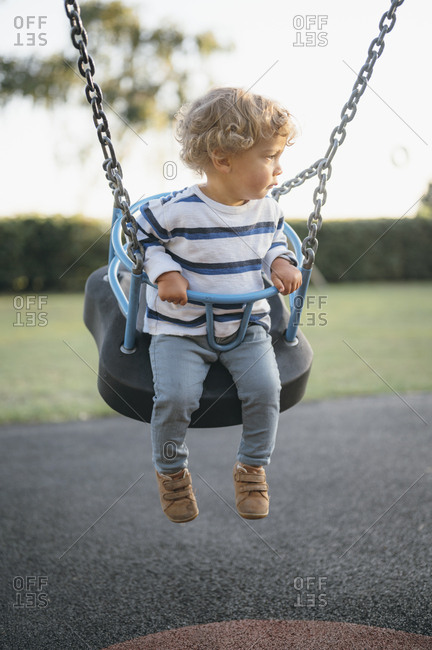 Young boy swinging on playground.