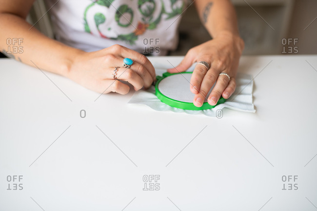 Woman attaching fabric to an embroidery hoop