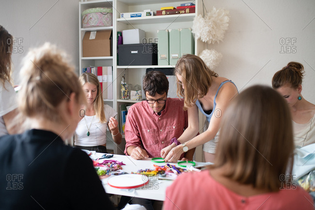 Woman showing a man how to set up his embroidery hoop at a cross-stitching class