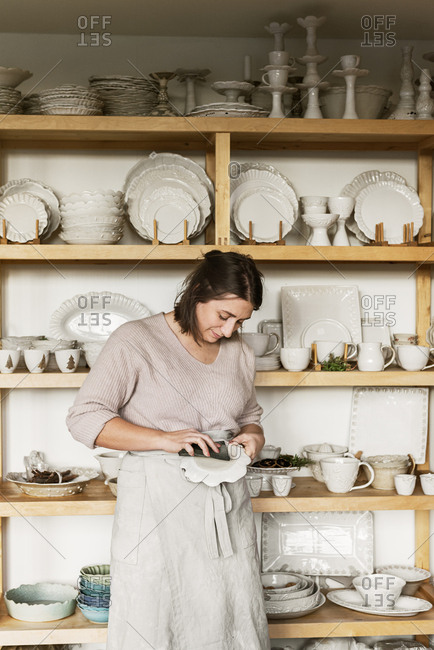 Woman cleaning pottery - Offset Collection
