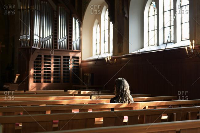 Priest sitting on pew in church