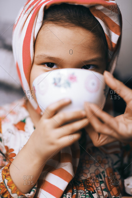 Portrait of a playful girl wearing striped headband and drinking from the cup