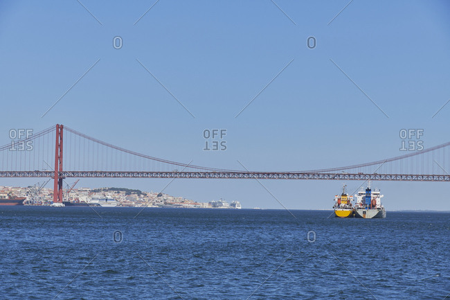 Two large ships in the Tagus River by the 25th of April bridge, Lisbon, Portugal