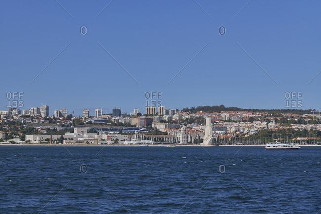 Lisbon, Portugal - September 10, 2019: The Tagus River with view of the Discoveries Monument with Cultural Center and Belem neighborhood and Jeronimos Monastery in background