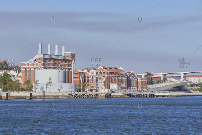 Lisbon, Portugal - September 10, 2019: The MAAT Museum of Architecture, Art and Technology overlooking tourists on the blue waterfront of the River Tagus
