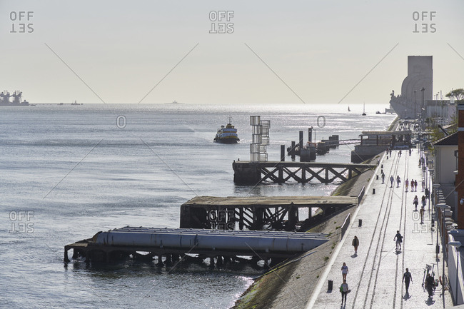 Lisbon, Portugal - September 10, 2019: Elevated view of a pedestrian walkway alongside the Tagus river and Monument of discovery