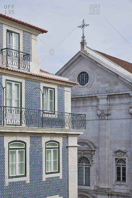 Facade of building with blue and green pattern tiles and Saint Nicholas Church in Lisbon, Portugal
