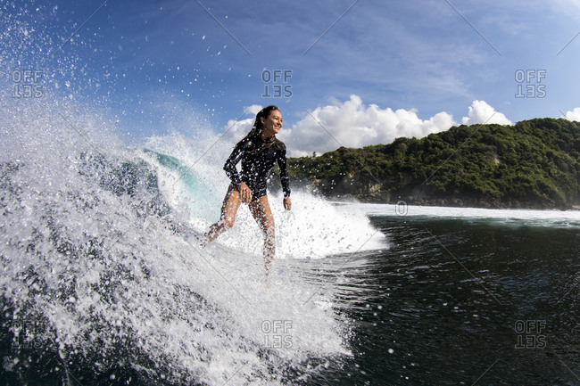 A young woman surfs a perfect wave in Indonesia