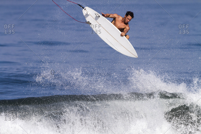 A surfer does an aerial while surfing in Bali, Indonesia