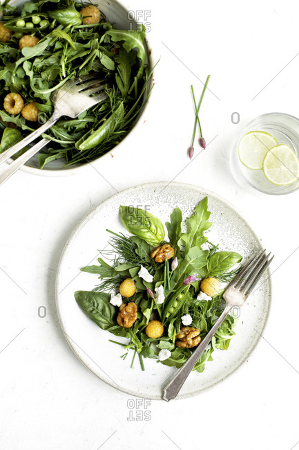 Arugula salad with golden raspberries and coconut vinaigrette served on a plate