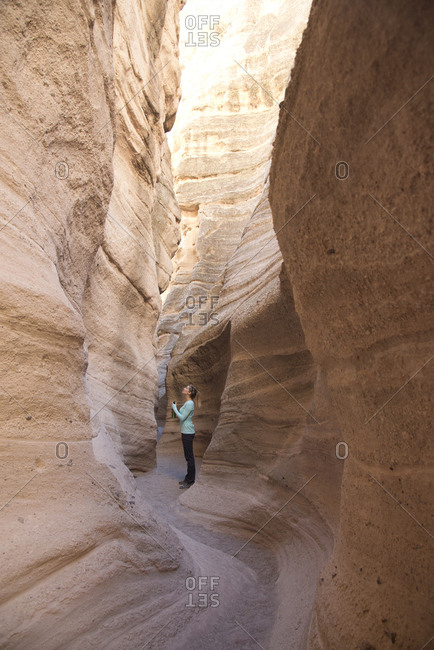 Woman admiring a sandstone slot canyon in Kasha-Katuwe Tent Rocks National Monument, New Mexico
