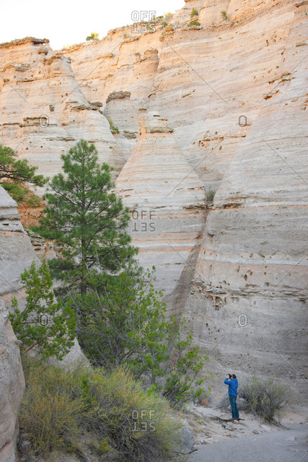 Man photographing in a canyon, within Kasha-Katuwe Tent Rocks National Monument, New Mexico