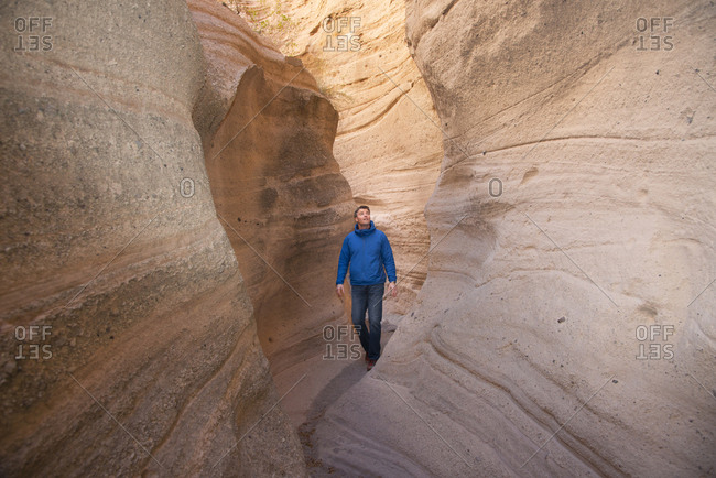 Man admiring a sandstone slot canyon in Kasha-Katuwe Tent Rocks National Monument, New Mexico