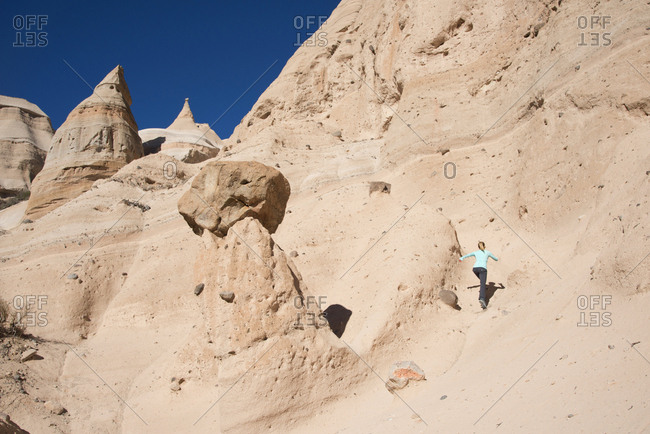 Woman running up a trail at Kasha-Katuwe Tent Rocks National Monument, New Mexico