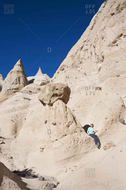 Woman resting along a path in Kasha-Katuwe Tent Rocks National Monument, New Mexico