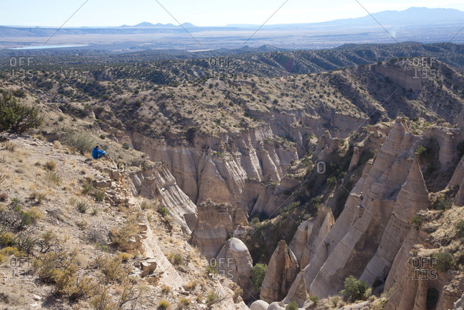 Hiker resting on cliff overlooking Kasha-Katuwe Tent Rocks National Monument, New Mexico