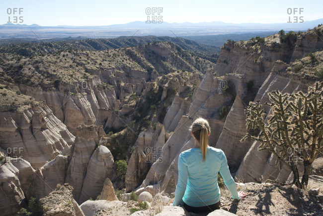 Woman sitting on a bluff looking out over Kasha-Katuwe Tent Rocks National Monument, New Mexico