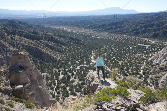 Woman standing on a bluff looking out over Kasha-Katuwe Tent Rocks National Monument, New Mexico