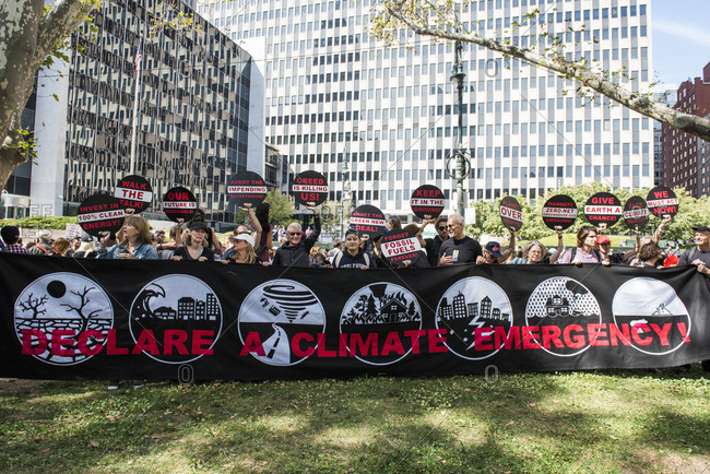 New York City, New York - September 20, 2019: Group of people holding signs and large banner at the Global Climate Strike