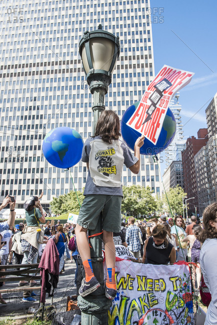 New York City, New York - September 20, 2019: Protester on a lamppost at the Global Climate Strike