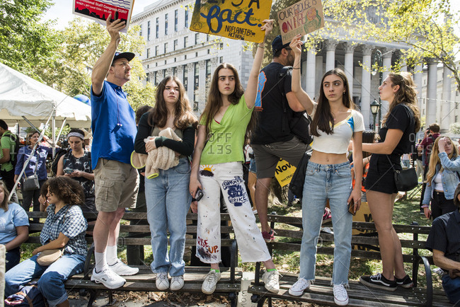 New York City, New York - September 20, 2019: People standing on benches holding signs in protest at the Global Climate Strike