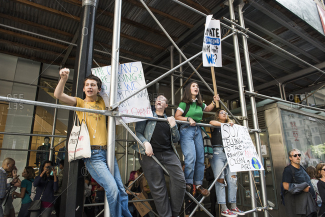 New York City, New York - September 20, 2019: People climbing on scaffolding with signs at the Global Climate Strike
