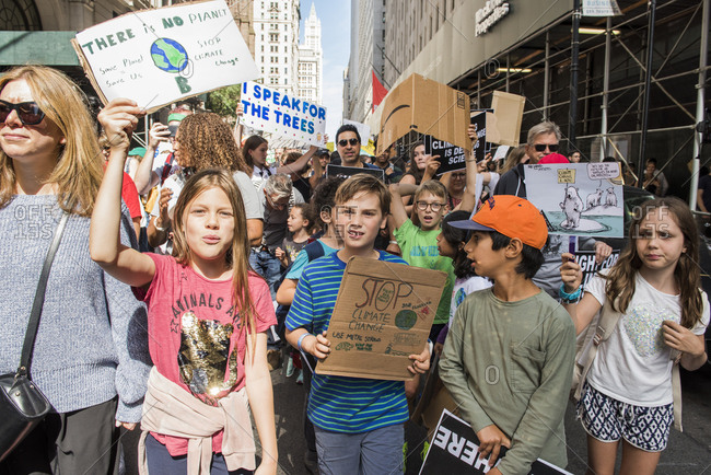New York City, New York - September 20, 2019: Group of kids holding signs while marching at the Global Climate Strike