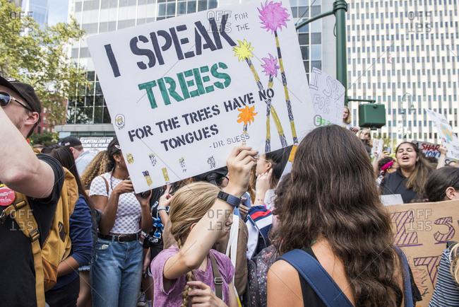 """New York City, New York - September 20, 2019: Girl holding """"I speak for the trees"""" sign at the Global Climate Strike"""
