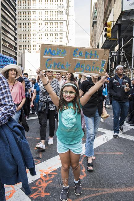 "New York City, New York - September 20, 2019: Girl holding ""Make earth great again!"" sign at the Global Climate Strike"