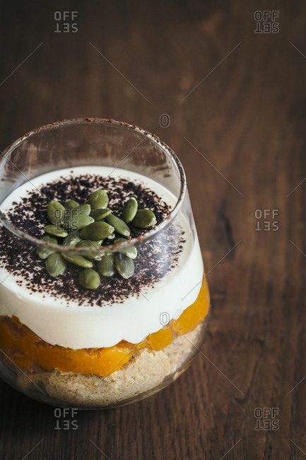 Close-up winter squash and spiced tiramisu cup on a wooden table