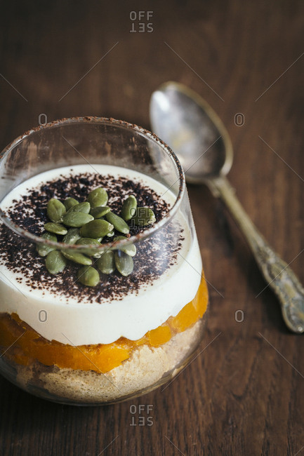 Close-up winter squash and spiced tiramisu cup with spoon on a wooden table