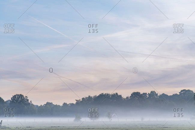 Clouds in sunrise sky and fog covering farmland